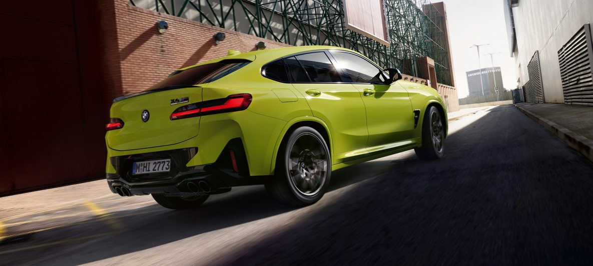 BMW X4 M Competition F98 LCI Facelift 2021 Sao Paulo Gelb Dreiviertel-Heckansicht zwischen Fabrikhallen fahrend